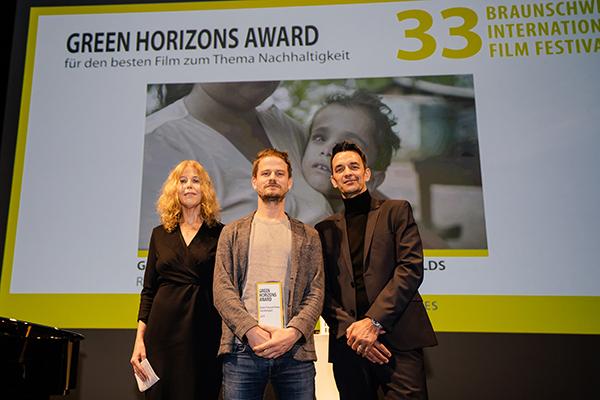 Eine Frau und zwei Männer auf einer Bühne bei einer Preisverleihung auf einem Filmfest