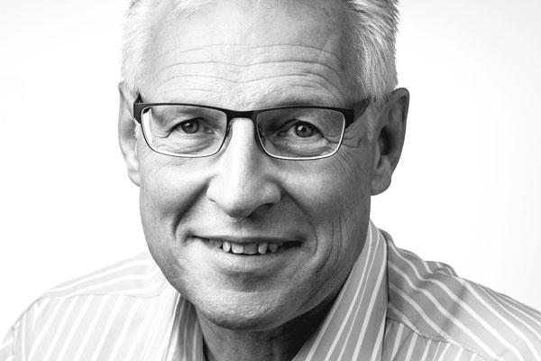 Gesicht eines sympathisch lächelnden Mannes mittleren Alters mit kurzen grauen Haaren und Brille