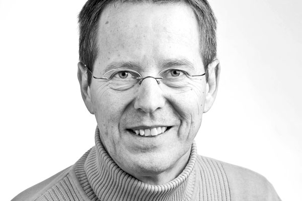 Gesicht eines sympathisch lächelnden Mannes mittleren Alters mit kurzen dunklen Haaren und Brille